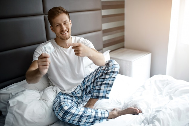Молодой сексуальный мужчина на кровати рано утром. он держит в руке презерватив и указывает на него. улыбается.