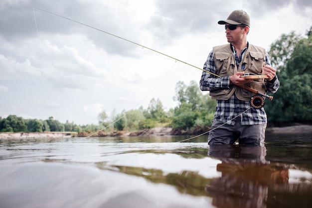Крутой рыбак стоит в воде и смотрит прямо вперед. он серьезен. парень держит в руках удочку и деревянный ящик с искусственными приманками и настоящими мухами. он собирается на рыбалку.
