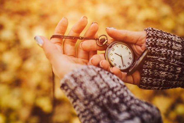 路上で秋の背景のクローズアップの手でアンティークのポケット時計