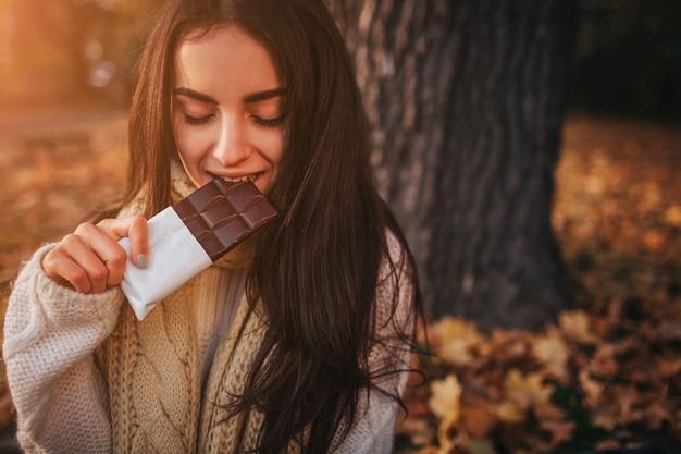 Красивая молодая брюнетка сидит на опавших осенних листьях в парке