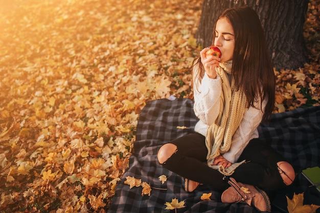 秋の公園で赤いリンゴを持つ女性。