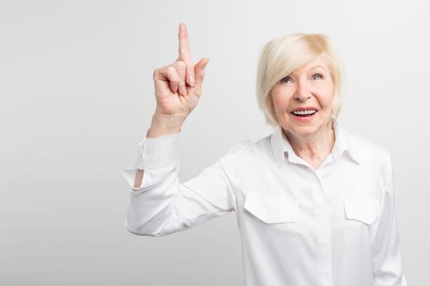 Славное изображение старухи стоя на белой стене и указывая вверх. блестящая идея пришла ей в голову. теперь она хочет это реализовать.