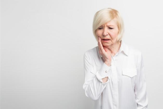 老婦人は歯痛に苦しんでいます。それは突然痛み始めました。彼女は歯医者に行く必要があります。白い背景で隔離