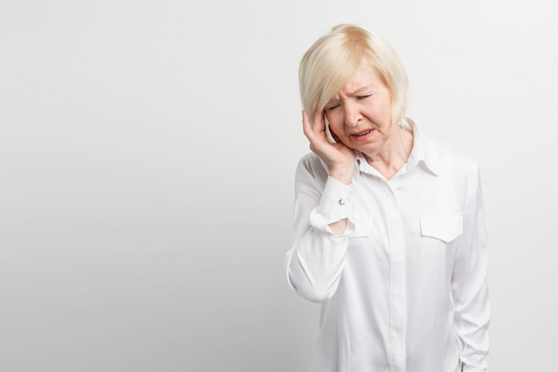 美しいと成熟した女性は彼女の手を彼女の頭に近づけています。彼女は、頭が痛い。彼女は安心を得るためにピルを服用する必要があります。