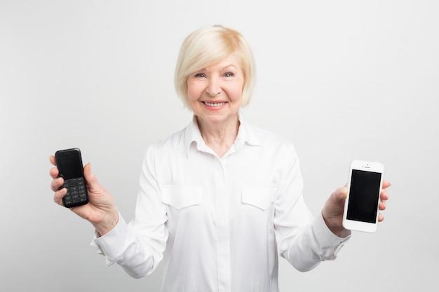 幸せな年配の女性は、ボタンと古い携帯電話と大画面の新しい携帯電話を保持しています。彼女はこれらの電話の両方を使用していましたが、新しい電話を使用して電話することを好みます。