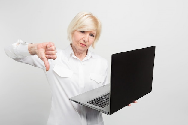 新しいラップトップを持つ成熟した女性の写真。彼女はそれをテストし、ラップトップが悪いことを認めました。それが彼女が大きな親指を見せている理由です。