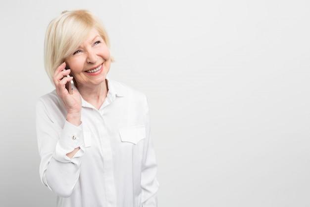 新しいスマートフォンを使用して家族に電話をかける女性の素敵な写真。彼女は新しいテクノロジーを愛し、できる限り新しいデバイスを使用しようとしています。