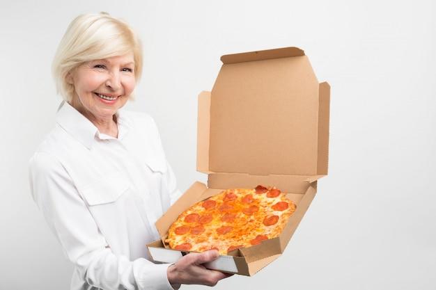 Отрежьте взгляд бабушки держа большую коробку вкусной пиццы. ей нравится нездоровая пища, она не здорова для людей. дама выглядит радостной и счастливой.