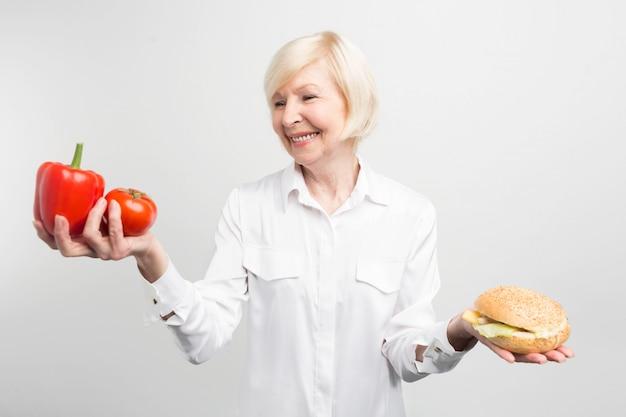 Картина дилеммы между хорошей и плохой едой. что лучше выбрать: два хороших перца или один вкусный гамбургер. ответ очевиден, но сделать его нелегко. изолированные на белом фоне