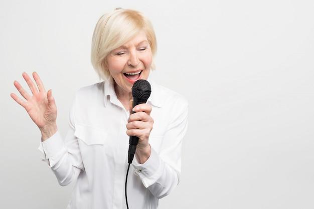 フレームの左側に立って、お気に入りの歌を歌っている素敵な女性。彼女はそれをするのが好きです。