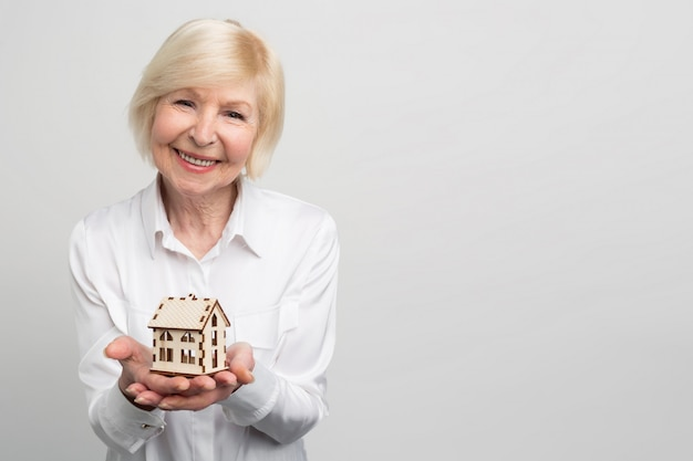 手に小さな家のおもちゃを持っている幸せで笑顔の女性の写真。彼女は現在若くなく、将来のためにいくつかの保証を持ちたいです。