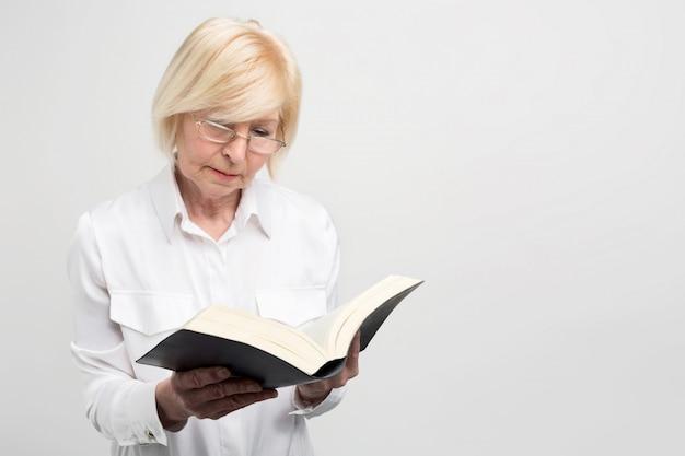 シニアビジネスの女性は部屋に立って本を読んでいます。それは非常に興味深いです。