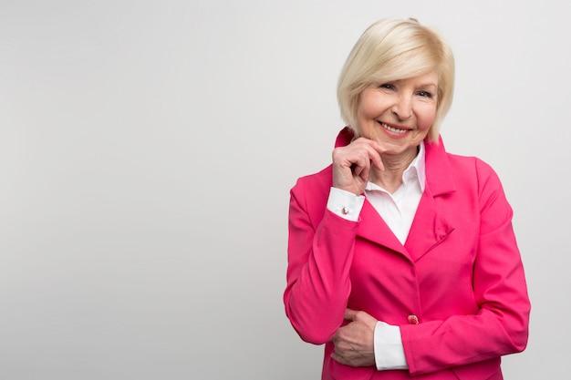 明るいコートを着たおしゃれでスタイリッシュなおばあちゃんの写真。彼女は明るい色を恐れていません。彼女は実験をするのが好きです。