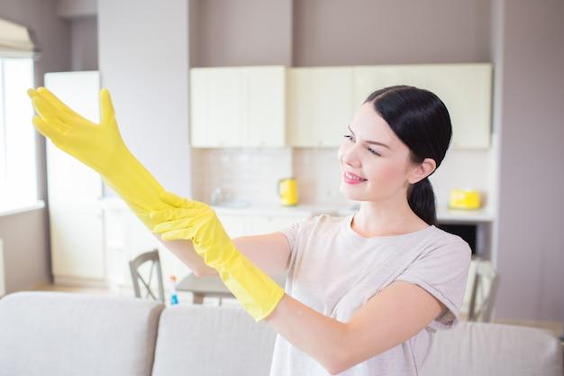 Изображение женщины стоит и надевает желтую перчатку на правой руке. она смотрит на это и улыбается. девушка стоит перед диваном в однокомнатной квартире.