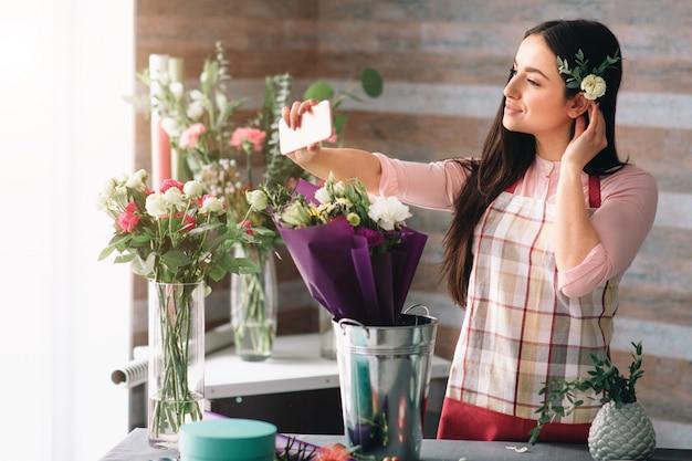 Женский флорист на работе: довольно молодая темноволосая женщина делает модный современный букет из разных цветов. женщины работают с цветами в мастерской. она делает селфи с цветами