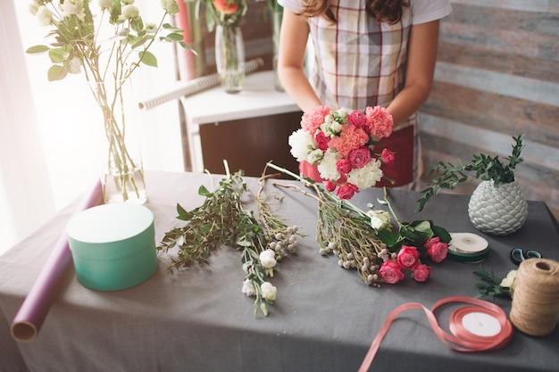 Женский флорист на работе: довольно молодая темноволосая женщина делает модный современный букет из разных цветов. женщины работают с цветами в мастерской