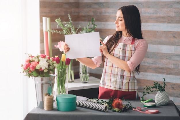 Женский флорист на работе: довольно молодая темноволосая женщина делает модный современный букет из разных цветов. женщины работают с цветами в мастерской. она показывает чистый лист бумаги