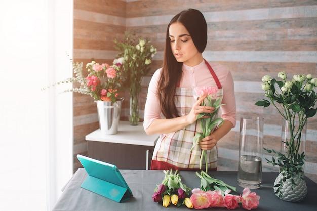 Женский флорист на работе: довольно молодая темноволосая женщина делает модный современный букет из разных цветов. женщины работают с цветами в мастерской. она использует планшет на работе.