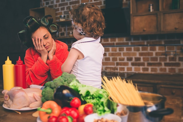 自宅で母を強調しました。家庭の台所で小さな子供を持つ若い母親。彼女の赤ちゃんの世話をしながら多くのタスクを行う女性