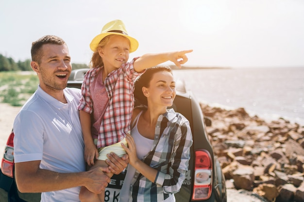 スーツケースとバッグで開かれた車のブーツの近くに立っている若いカップル。お父さん、お母さん、娘は海や海、川で旅行しています。自動車による夏の乗り物