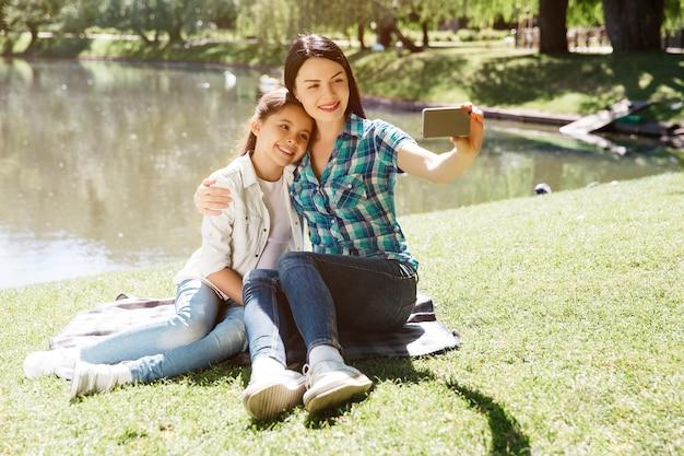 ママと娘が自分撮りを撮っている素敵な写真。彼らは池の近くの毛布の上に座っています。女性は携帯電話を保持しています。彼らはそれを見て、笑っています。女の子がポーズを取っています。