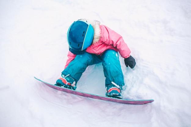 スノーボードウィンタースポーツ。暖かい冬の服を着て雪で遊ぶ子供女の子。冬