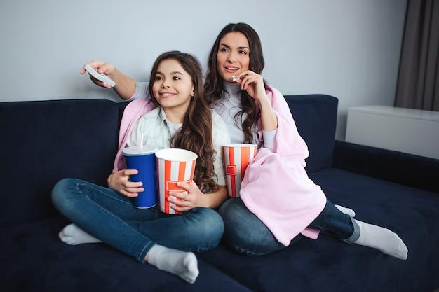 美しいブルネットの白人の母と娘は部屋に一緒に座っています。彼らは映画を見る。人々はポップコーンバスケットとコーラカップを持っています。大人はリモコンを持っています。落ち着いて集中しています。