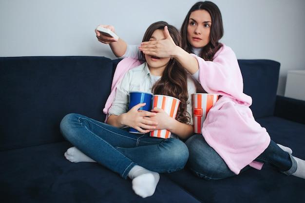 美しいブルネットの白人の母と娘は部屋に一緒に座っています。ママは少女の目を覆った。彼女はリモートコントロールを保持し、嫌悪感を楽しみにしています。娘はバセットポップコーンとコーラを保持します。