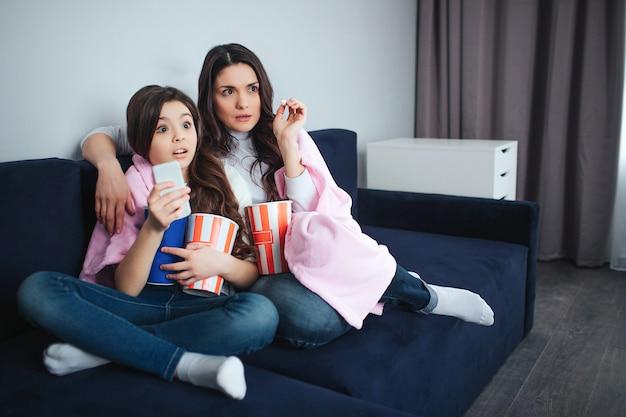 美しいブルネットの白人の母と娘は部屋に一緒に座っています。怖い大人と小さな女性は映画を見て、ポップコーンを食べます。おびえた。