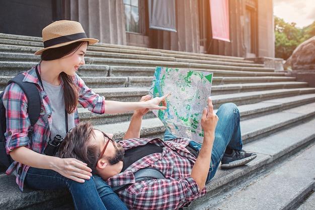 階段の上の若い観光客の素敵な写真。彼女はそこに座って地図上を指しています。彼は地図を持ち、女性の膝の上に横たわっています。