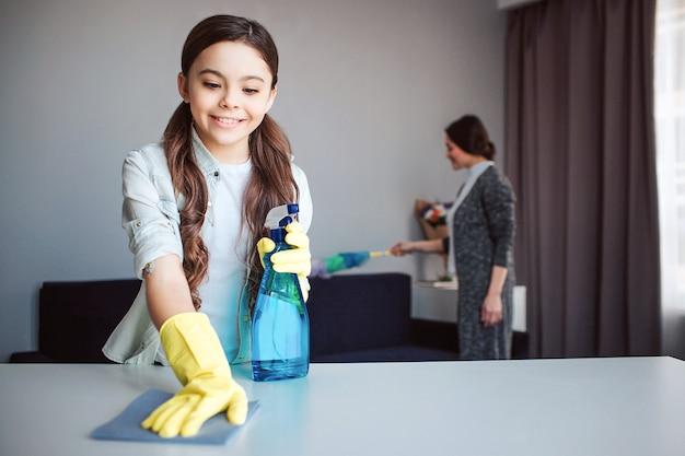 美しいブルネットの白人の母と娘が部屋で一緒に掃除します。女の子は手でスプレーを保持し、テーブルをきれいにします。彼女は黄色い手袋を着用しています。彼女のお母さんは後ろのほこりを吹き飛ばします。