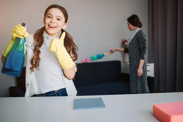 美しいブルネットの白人の母と娘が部屋で一緒に掃除します。女の子はスプレーを手に保持し、大きな親指を現します。彼女はカメラを見て笑顔します。若い女性の後ろに立って、ほこりを吹き飛ばします。
