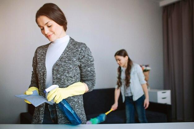 美しいブルネットの白人の母と娘が部屋で一緒に掃除します。スポンジに若い女性のスプレー。女の子は後ろに立ってほこりを吹き飛ばします。
