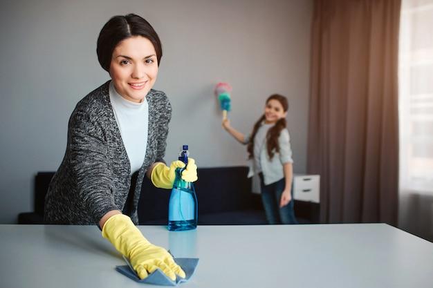 美しいブルネットの白人の母と娘が部屋で一緒に掃除します。陽気な若い女性が机を洗うし、スプレーを保持します。女の子は後ろに立ってほこりを吹き飛ばします。