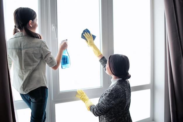美しいブルネットの白人の母と娘が部屋で一緒に窓を掃除します。女の子はスプレーを使用します。若い女性洗濯ウィンドウ。彼らは一緒に働きます。