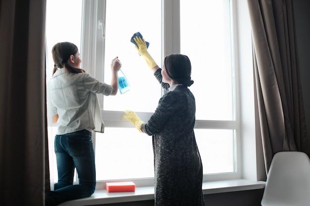 美しいブルネットの白人の母と娘が部屋で一緒に窓を掃除します。ハードワーキングガールはスプレーを使用します。若い女性洗濯ウィンドウ。彼らは一緒に働きます。