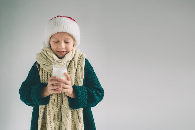 女の子は白に孤立したミルクの新鮮なガラスを飲んでいます。