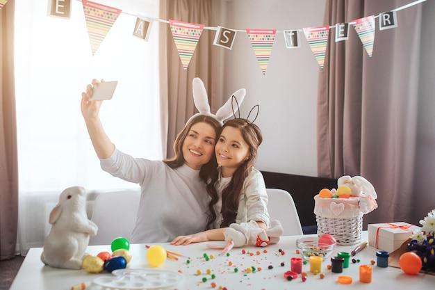若い母親と娘はイースターの準備をします。彼らは部屋に座って、電話のカメラで自分撮りをします。テーブルの上の絵と装飾とカラフルな卵。イースターバニー。