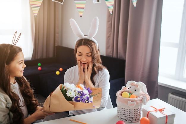 母と娘は一緒にイースターの準備をします。女の子は母親に花の美しい花束を与えます。彼女は驚いているようです。バスケットとテーブルの上のプレゼント。