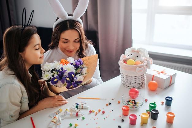 Молодая женщина и ее дочь готовятся к пасхе. они пахнут цветами вместе. краска с конфетами и украшения на столе. дневной свет.