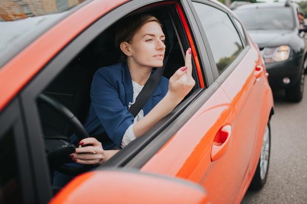 Женщина испытывает стресс на дороге. показывает факт в окне. большие пробки. деловая женщина опаздывает на работу
