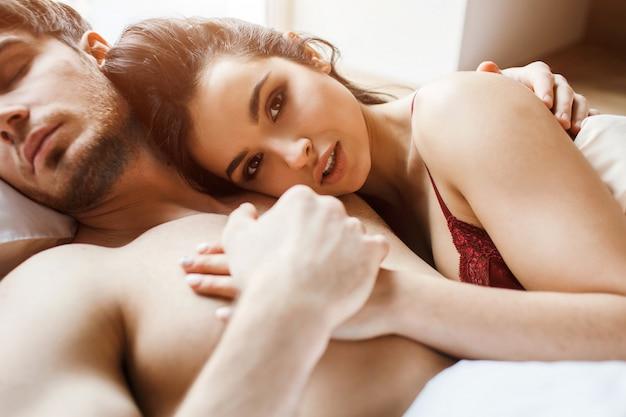 Молодая сексуальная пара имеет близость на кровати. отрежьте взгляд красивой женской брюнетки смотря камеру и усмехнитесь немного. он держит ее за руку. спать вместе. женщина лежит на его груди.