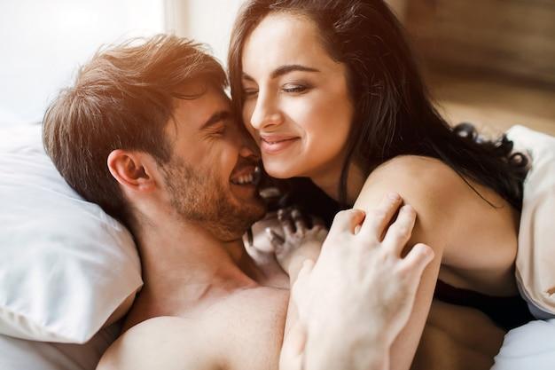 若いセクシーなカップルは、ベッドに親密さを持っています。男と笑顔の上に横たわる女性の美しい写真。ベッドで一緒に時間を過ごす。優しい人たち。