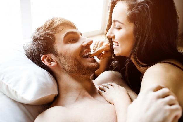 若いセクシーなカップルは、ベッドに親密さを持っています。一緒に横になって笑顔。男の女。美しいセクシーな魅力的な人々。明け。