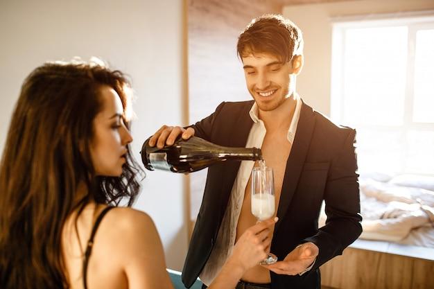 リビングルームで若いセクシーなカップル。スパークリングワインを女性のグラスに注ぐスーツの陽気な素敵なビジネスマン。部屋で一緒に。親密な後のセクシーなスープ。