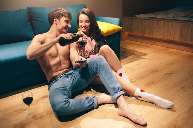 夜のキッチンで若いセクシーなカップル。ワインを飲みながら一緒に時間を過ごす。ホットの魅惑的な男と女の幸せ。陽気な笑顔。赤ワインをグラスに注ぐ男。