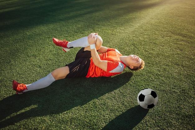 Молодой футболист лежа на лужайке и держит ногу. он тянет это к себе. парень чувствует боль в колене. мяч лежал рядом с ним.