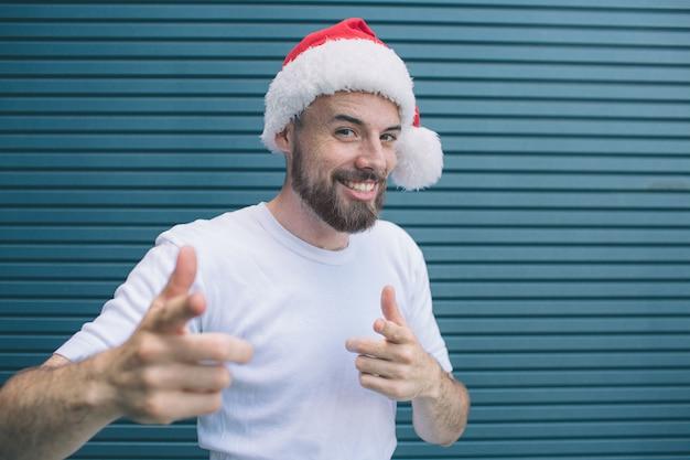 サンタの帽子を持つ肯定的な男は笑っています。彼はカメラを指しています。ひげを生やした男は幸せです。ストライプに分離