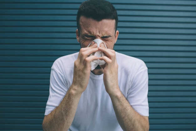 男はくしゃみをして、鼻と口をナプキンで覆っています。彼は気分が悪い。ストライプに分離