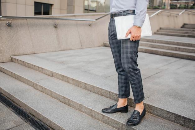 Вырезать вид стильный мужчина стоять и ставить. он держит ноутбук с рукой. молодой человек стоит на ступеньках.
